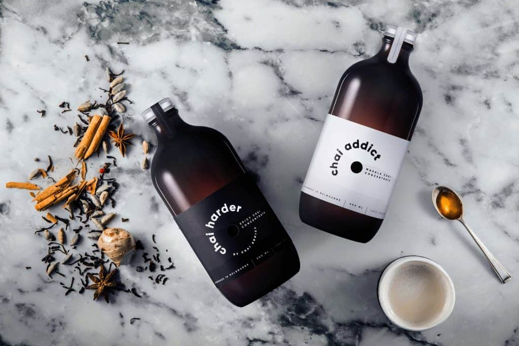 flatlay image of chai addict and chai harder chai concentrate bottles with whole spices