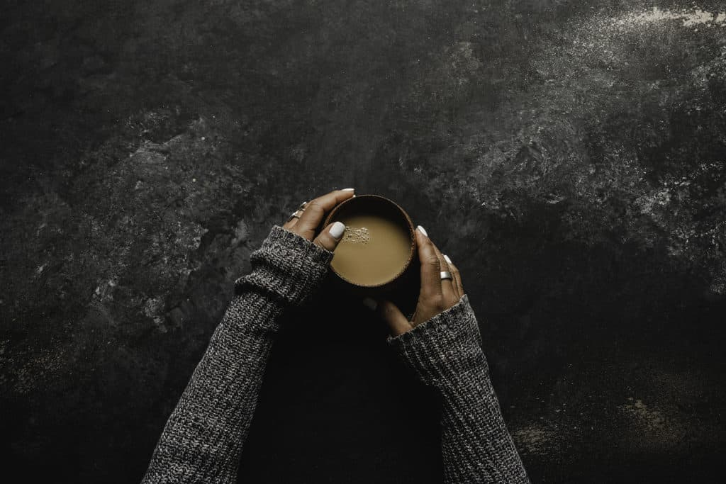hands wrapped around cup of white chocolate chai