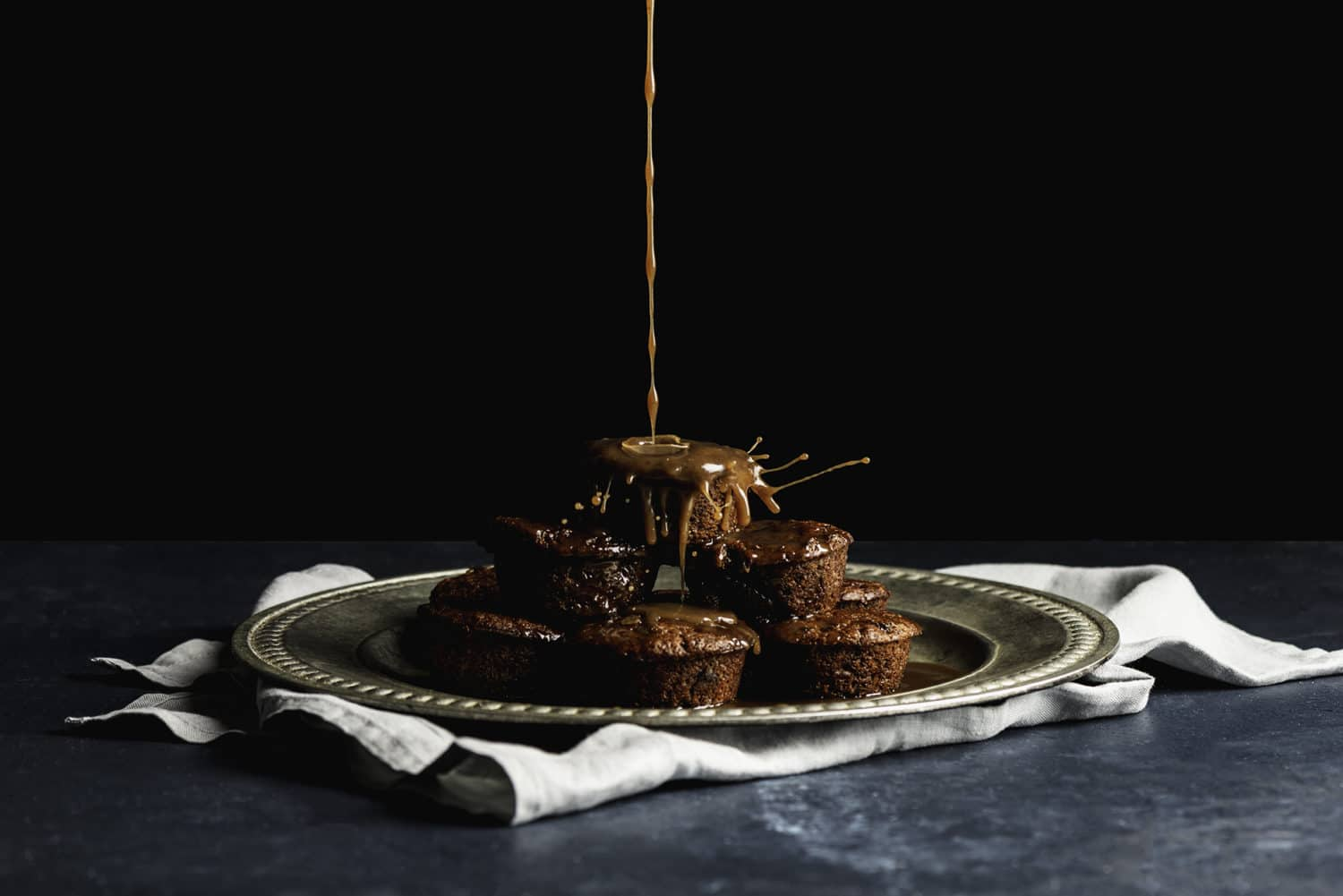 chai date muffins being drizzled with caramel sauce